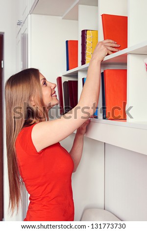 pretty woman getting the book from the shelf - stock photo