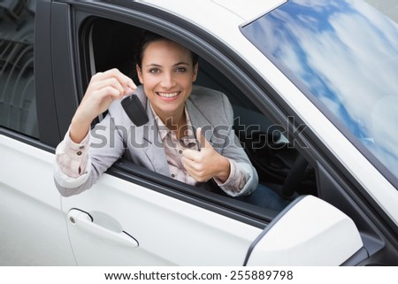 Pretty woman giving thumbs up while holding key in her car - stock photo