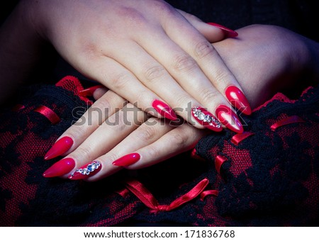 Pretty woman hand with red nails and lingerie - stock photo