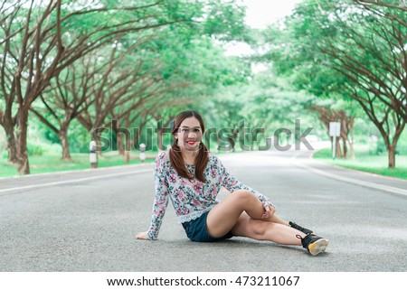 Pretty woman has a beautiful smile sit on the road under tunnel trees sweet tone,bright tone