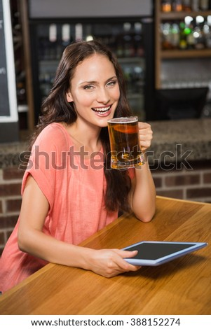 Pretty woman having a beer and looking at tablet in a pub
