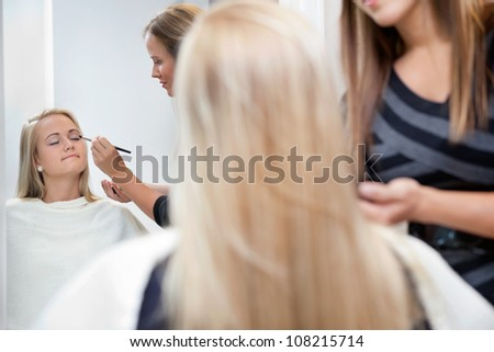Pretty woman having eye shadow applied by a female makeup artist - stock photo
