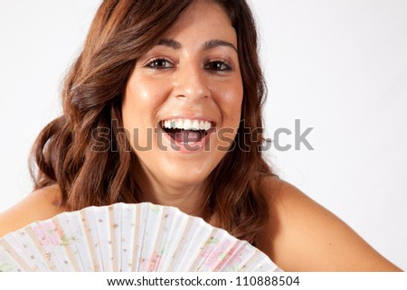 Pretty woman hiding her torso behind a fan with a playful smile - stock photo