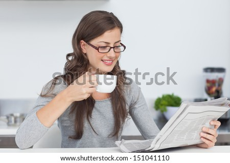 Pretty woman holding a cup of coffee and reading a newspaper - stock photo