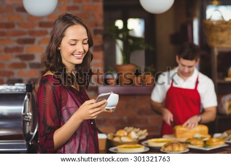 Pretty woman holding a cup of coffee and texting at the cafe