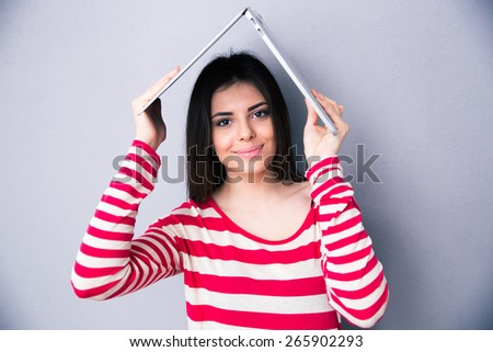 Pretty woman holding a laptop above her head like a roof over gray background. Looking at the camera