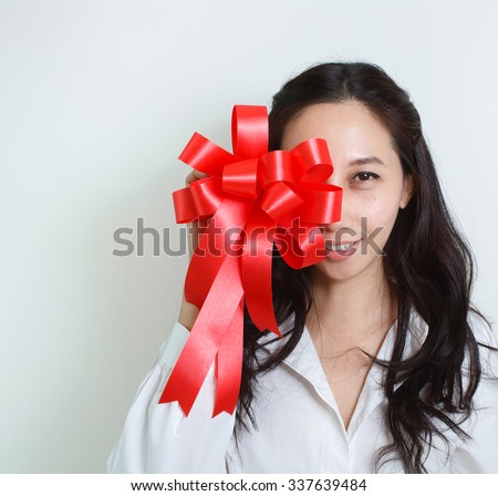 Pretty woman holding a red ribbon - stock photo