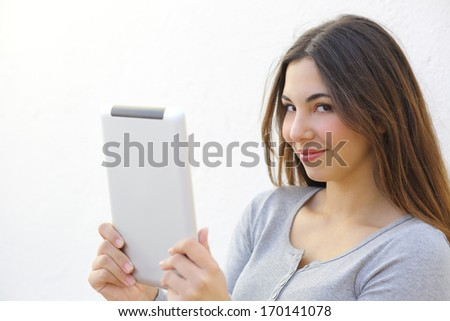 Pretty woman holding a tablet and looking at camera on a white wall - stock photo