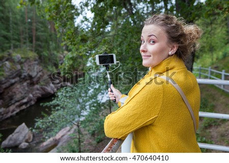 Pretty woman holding smartphone on selfie stick and looking at camera