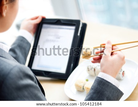 Pretty woman holding sushi with chopsticks and reading news using her tablet computer and free wifi at cafe on business lunch offer - stock photo