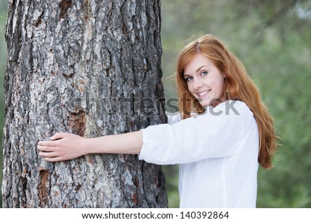 Pretty woman hugging a tree standing with her arms around the trunk smiling at the camera to show her appreciation - stock photo