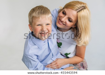 Pretty woman hugging her son. Cute blonde laughing boy with his mother indoors. - stock photo