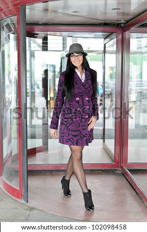 Pretty woman in a coat going thru revolving doors - stock photo
