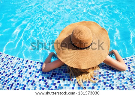 Pretty woman in a hat enjoying a swimming pool - stock photo