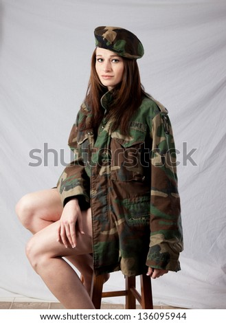 Pretty woman in a military camouflage jacket and beret hat, with bare legs emerging from the bottom of the jacket, looking at the camera with a friendly, sexy smile