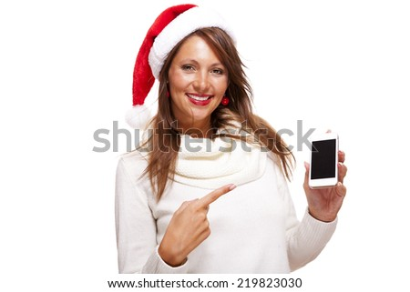 Pretty woman in a Santa hat reading a sms on her mobile phone sending Christmas wishes smiling with pleasure at the news, isolated on white - stock photo