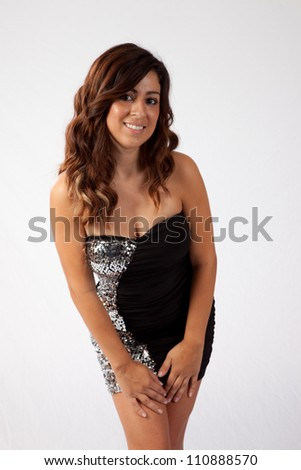 Pretty woman in a sexy little black dress, with her hands on her legs and a happy smile for the camera - stock photo