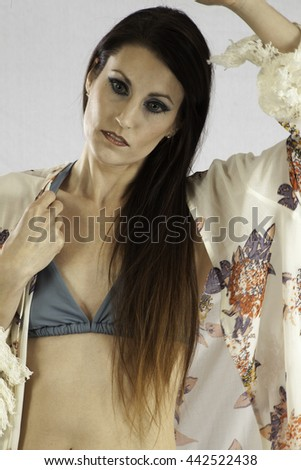 Pretty woman in a swim suit and a cover up over it, looking thoughtful - stock photo