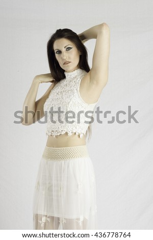 Pretty woman in a white dress,  looking thoughtfully at the camera  while arranging her hair
