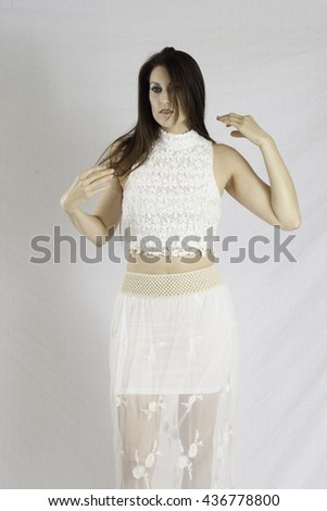 Pretty woman in a white dress,  looking thoughtfully at the camera  while arranging her hair - stock photo