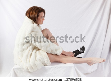 Pretty woman in  a white fur coat, putting on her shoes