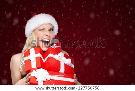 Pretty woman in Christmas cap holds a set of presents, isolated on purple