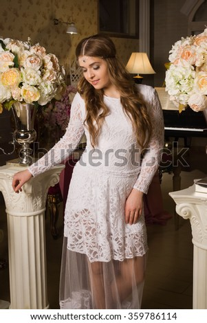Pretty woman in evening dress posing in a vintage interior