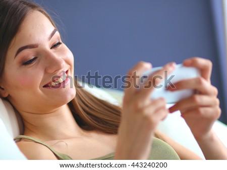 Pretty woman in her living room lying on the couch sending mess - stock photo