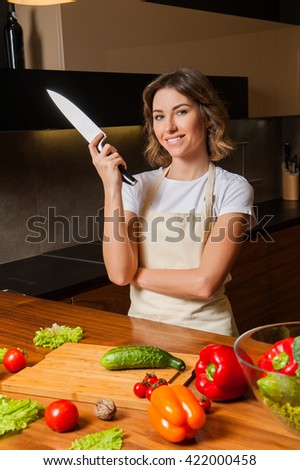 Pretty woman in kitchen with knife looking to the camera - stock photo