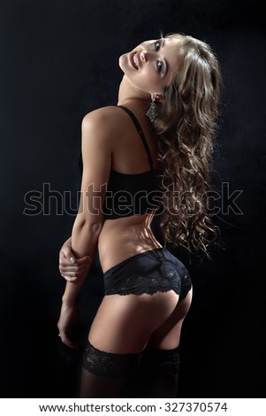 pretty woman in lingerie and stockings shows her buttocks on black background - stock photo