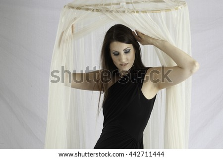 Pretty woman in little black dress behind sheer curtains - stock photo