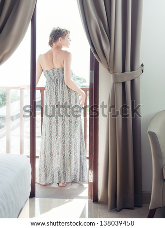 Pretty woman in long dress standing on a balcony - stock photo