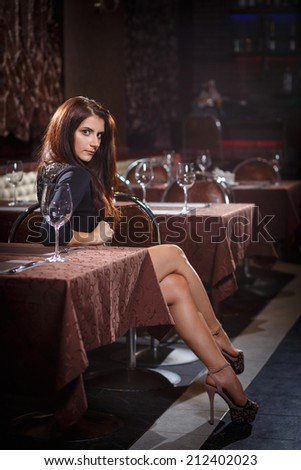 pretty woman in nightclub sitting alone at the table