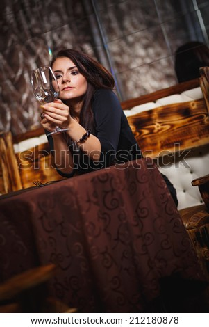 pretty woman in nightclub sitting alone have a glass of wine - stock photo