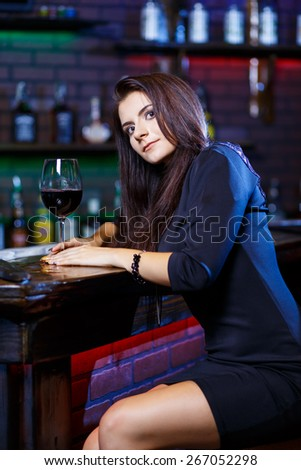pretty woman in nightclub sitting alone have a glass of wine