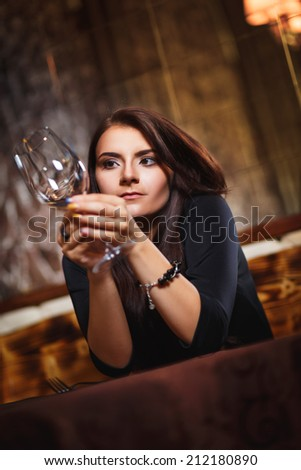 pretty woman in nightclub sitting alone with empty glass - stock photo