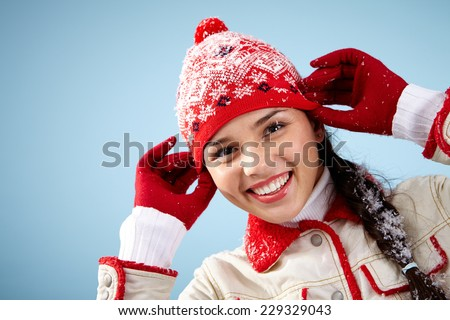 Pretty woman in red and white winterwear looking at camera with toothy smile