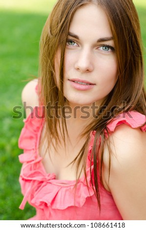 Pretty woman in red dress sitting on park or garden at summer - stock photo