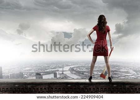 Pretty woman in red dress with axe in hand