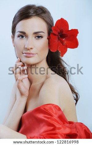 pretty woman in red with fresh red flower in the hear touched her face - stock photo
