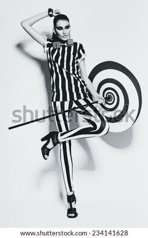 pretty woman in striped top and leggings with umbrella in studio - stock photo