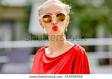 Pretty woman in sunglasses blowing lips kiss - stock photo