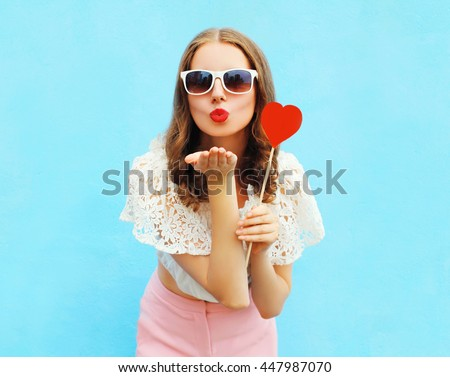 Pretty woman in sunglasses with red heart lollipop sends an air kiss over colorful blue background - stock photo