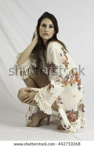 Pretty woman in swim suit and wrap, squatting and  looking thoughtful  with her hand in her hair - stock photo