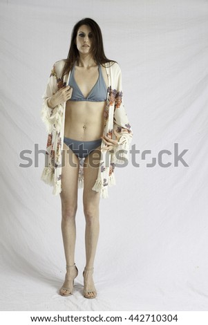 Pretty woman in swim suit and wrap, standing and looking thoughtful   - stock photo