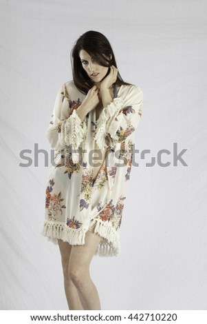 Pretty woman in swim suit and wrap, standing and looking thoughtful with her hand in her hair - stock photo