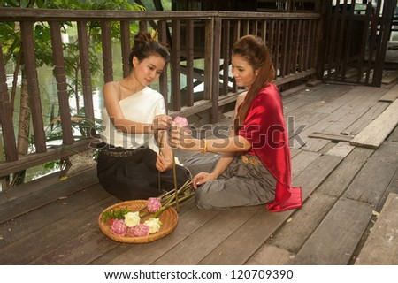 Pretty woman in Thai style clothes in posing artificial flowers. - stock photo