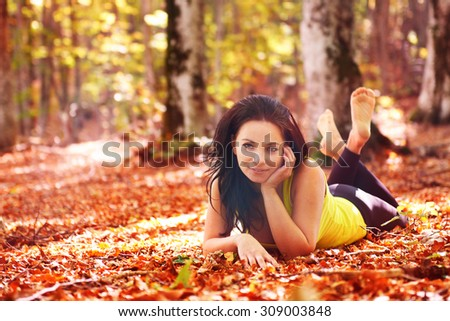 Pretty woman in the autumn forest laying on orange leaves