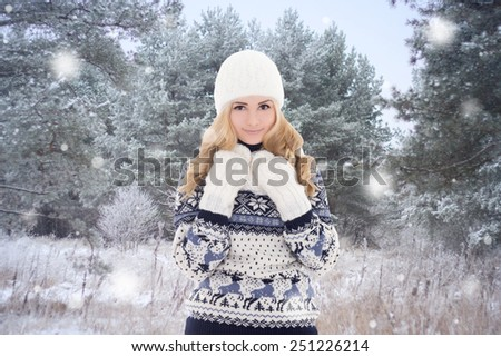 pretty woman in warm clothes posing in winter forest - stock photo