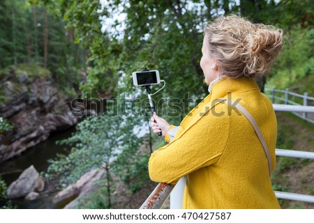 Pretty woman in wearing yellow coat making picture of nature on a smartphone with selfie stick